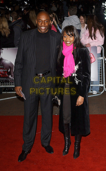 "JOHN FASHANU & GUEST.""Get Rich Or Die Tryin'"" UK film premiere at Empire leicester Square. London, UK..January 17th, 2006.Ref: BEL.full length black suit pink scarf.www.capitalpictures.com.sales@capitalpictures.com.© Capital Pictures."