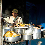 """The Saturday market in Otavalo is the largest in Ecuador. Otavalo is situated in a beautiful valley between the Imbabura volcano (4,609 m) and Mount Cotacachi (4,939 m). Very early in the morning the people of the surrounding mountains come to the city market with their ware. From 5 pm there is a livestock market where cattle, pigs, poultry and small animals like rabbits and guinea pigs are sold. The guinea pig market is the longest lasting market. Women with baskets and boxes with guinea pigs try to sell their wares. Guinea pigs are inspected, particularly by their size and gender, not by their """"pettability"""". Guinea pigs (cuyes in Spanish) is in this part of Ecuador a delicacy, eaten with rice, potato and vegetables. For a good healthy guinea pig eagerly 4-8 dollar is paid. Usually they are bought for breeding. The selling starts around 5 am and lasts until 4 in the afternoon. Then the cows and pigs have long gone home. At midday the market gradually eliminates. The guinea pigs, hens and chickens are the latest to leave in bags with a new owner off the market."""