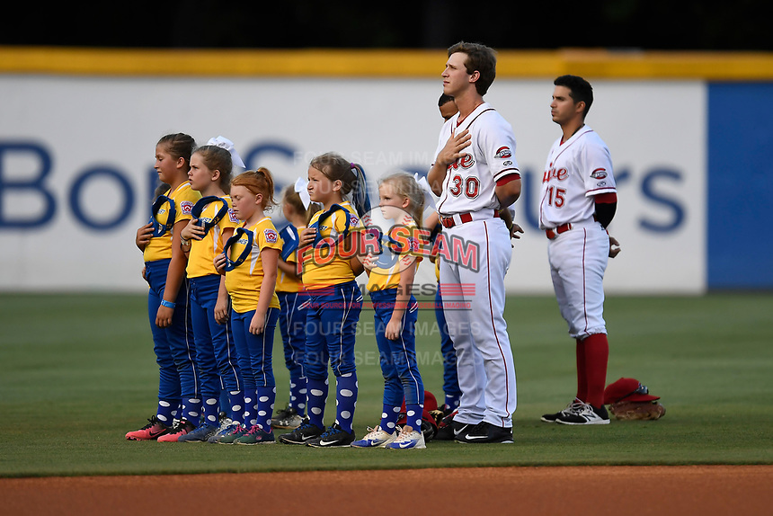 Outfielders Ryan Scott (30) and Chris Madera (15) of the Greenville Drive listen to the National Anthem with youth softball players before a game against the Columbia Fireflies on Thursday, June 15, 2017, at Fluor Field at the West End in Greenville, South Carolina. Columbia won, 7-2. (Tom Priddy/Four Seam Images)