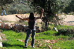 A Palestinian protester uses a slingshot to throw stones at Israeli soldiers during clashes in the West Bank village of Bilin, west of Ramallah, following a march organized in solidarity with the people of the village against the construction of settlements and the confiscation of their land on December 26, 2014. Photo by Shadi Hatem