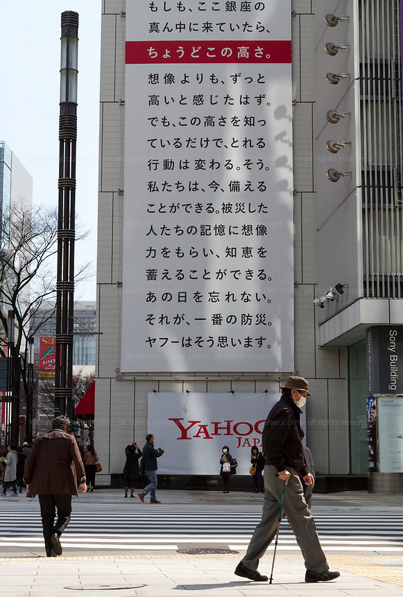 A large billboard on the side of the Sony Building in Ginza marks the sixth anniversary of the March 11th 2011 earthquake and tsunami in Tohoku. Ginza, Tokyo, Japan. Friday March 10th 2017 The billboard was created by Yahoo and shows the asks passers by to remember the disaster and the nearly 16,000 people who died. the line marked in red shows the maximum height of the tsunami (16.7 metres at Ofunato in Miyagi prefecture. The billboard is on display until March 12th.