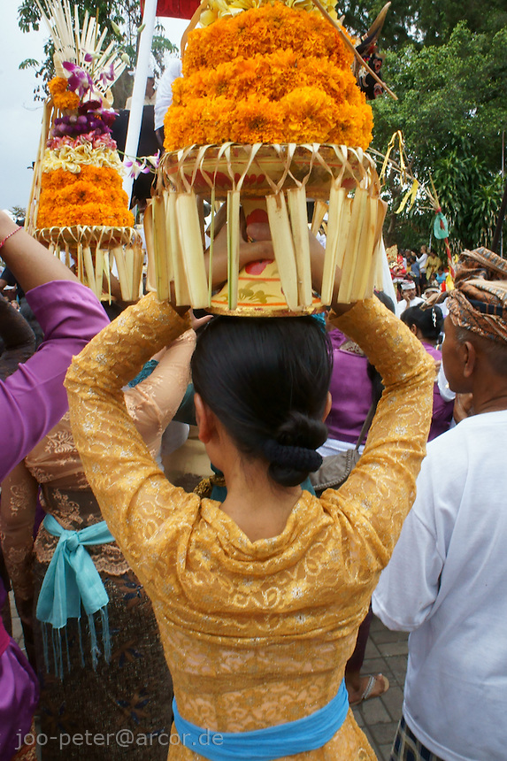 woman carrying offerings while cremation ceremonies,  September 17th 2011,  family Nyoman Budiana and others, Banjar Pande, Peliatan next to Ubud, Bali, archipelago Indonesia. Cremation ceremonies guide the spirit of the passed family member from underworld death realms to divine heavenly nature spirit life circle uprise of the death, becoming a divine ancestor to be reborn in the next generation of the family
