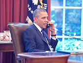 As seen through an outside window looking into the Oval Office, United States President Barack Obama speaks on a conference call hosted by the American Lung Association and other public health groups to discuss new commonsense steps to reduce carbon pollution from power plants in Washington, D.C. on Monday, June 2, 2014.<br /> Credit: Ron Sachs / Pool via CNP
