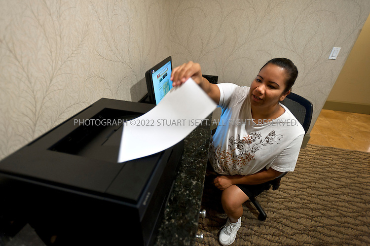 "9/27/2011--Seattle, WA, USA..Valerie Bayers, 34, from Vancouver, Canada, using the business center, just off the main lobby, at the Silver Cloud Hotel in Seattle, WASH. Bayers was visiting Seattle on vacation so did not have a laptop with her and needed to use the business center to print out information on a restaurant she wanted to visit...Business travelers armed with laptops, smartphones and wifi cards, are eschewing hotel business centers in favor of working in their rooms or the lobby, and hotels across the price spectrum have added the trappings of those business centers to where the guests are.  Hotel business centers are still used by travelers who have a document or boarding pass to print, or need to check email and don't have their laptop, but they will usually get in and out quickly, rather than spend hours working there. And the business centers themselves are likely to be small rooms with just a few computers and printers. The Silver Cloud Hotel in Seattle, part of a ten-hotel chain in the Northwest, offers up two workstations and two printers, ""and business people barely use them,"" said the hotel's general manager Chauncey DeVitis. The free WiFi and the copy machine behind the front desk seems to meet the needs of most business travelers these days, he said...©2011 Stuart Isett. All rights reserved."