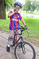 Polish boy age 8 resting on his bicycle wearing helmet and gloves. Paderewski Park Rzeczyca Central Poland