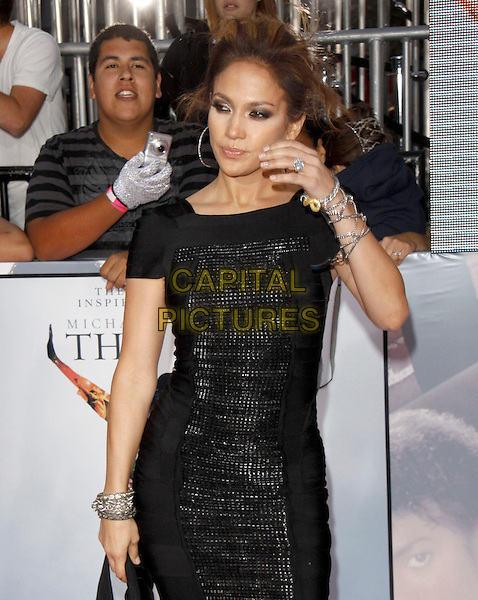 """JENNIFER LOPEZ.The Columbia pictures' L.A. Premiere of Michael Jackson's """"This Is It"""" held at The Nokia Theatre Live in Los Angeles, California, USA..October 27th, 2009.half length black dress chains bracelets silver hand hoop earrings hair up clutch bag .CAP/RKE/DVS.©DVS/RockinExposures/Capital Pictures."""