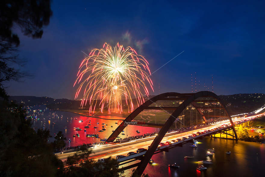 Colorful 4th of July fireworks paint the night sky over the 360 Bridge on Lake Austin as boats anchor in the lake to watch Austin's favorite fireworks display in celebration of our nations birthday, 4th of July holiday.