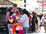 Mexican woman convinces tourist to purchase Papier-mâché flowers.