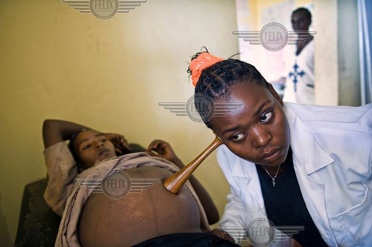 Tadelech Shibesha a health worker, listens to the heartbeat of Karababo Kiyo's unborn foetus at a health post in Kamba Umbu Village.