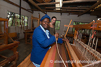 Africa, Swaziland, Malkerns.Nest organization artisan project, partnering with Rosecraft weaving  & local artisans to help market their products to global markets and better sustain their local community. Rebecca van Bergen, Nest founder, looks on as women weave at their looms.