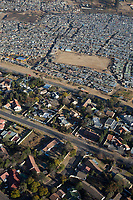 JOHANNESBURG, SOUTH AFRICA - JULY 19: An aerial view of the poor black squatter camp Kya Sands, home to South Africans and many African Immigrants on July 19, 2018 in Johannesburg, South Africa. Across the road Bloubusrand, a middle class area with larger houses and swimming pools. South Africa has one of the highest income differences in the world and the country is struggling with a high unemployment rate and low growth rate. (Photo by Per-Anders Pettersson/Getty Images)