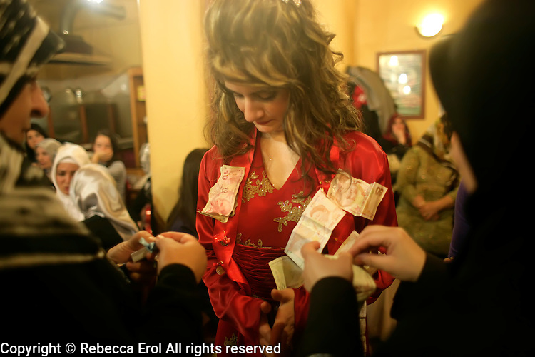 Turkish bride having money pinned to her by guests at pre wedding celebration or kina gecesi in Istanbul, Turkey