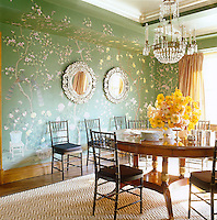 In the dining room an ormolu and cut-glass chandelier is suspended above an antique mahogany table and the pair of Venetian mirrors on the Chinoiserie-inspired wallpaper were Paris flea-market finds