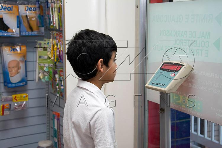 Menino se pesa em balança de farmácia, São Paulo - SP, 08/2016.