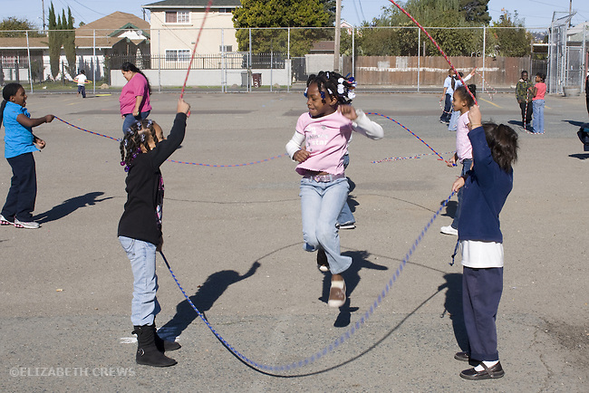 Oakland CA 2nd grade girl students (African American and Latina) jumping rope at recess