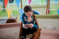 Thursday  29 May 2014, Hay on Wye, UK<br /> Pictured: A man reads and shelters from the rain at the Hay festival <br /> Re: The Hay Festival, Hay on Wye, Powys, Wales UK.