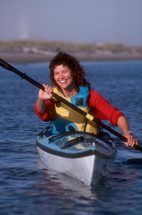Sea kayaker woman paddling toward camera, Port Townsend, Puget Sound, Washington State, USA