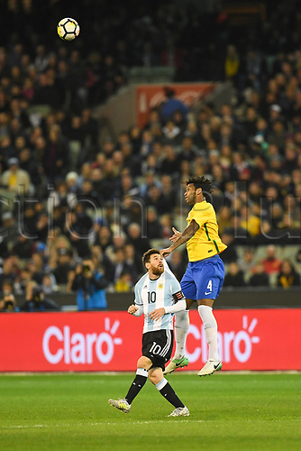 June 9th 2017, Melbourne Cricket Ground, Melbourne, Australia; International Football Friendly; Brazil versus Argentina; Carlos Gilberto of Brazil holds onto Lionel Messi of Argentina whilst jumping for the ball