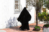 Muslim woman in traditional niqab veil clothing walking in the area of Kariye Muzesi, Edirnekapi in Istanbul, Republic of Turkey