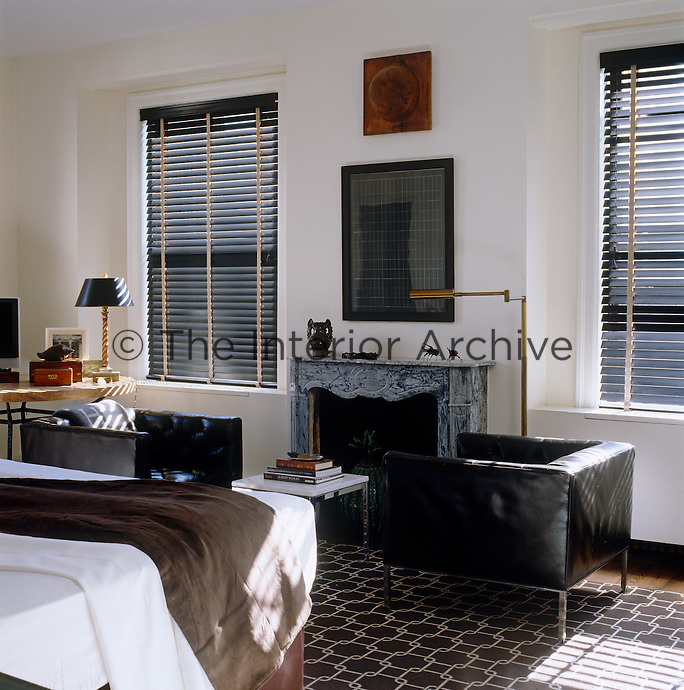 In this bedroom two contemporary black leather armchairs are arranged in front of an antique veined marble fireplace with the windows on either side screened in co-ordinating black Venetian blinds