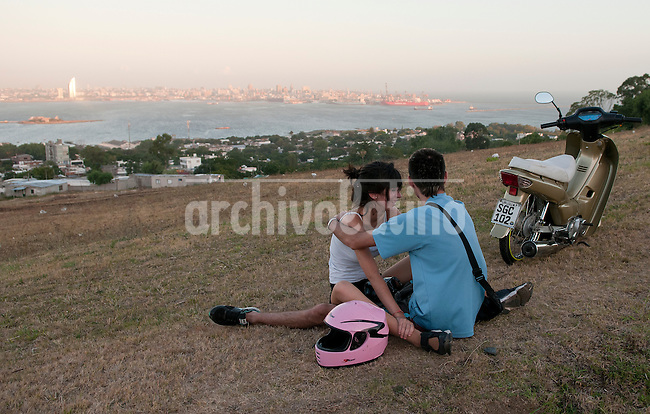 "A couple sits in the grass in the ""Cerro of Montevideo"". In the back, Montevideo Bay and skyline. Montevideo, Uruguay. Matilde Campodonico/Archivo Latino"