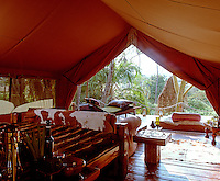 A tented bedroom rustically furnished has a deck beyond with a sun lounger and comfortable mattress