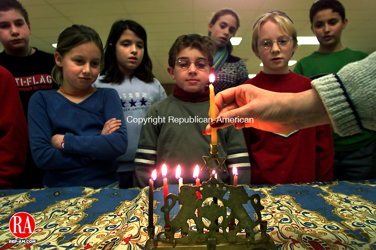 TORRINGTON, CT  12/04/02  1204BS05.02--Beth El Synagogue Religious School principal Marcia Lowe places the Chamesh back in place after lighting six candles representing six days of Hanukkah as children from the class watch the ceremony. Children from left are: Ross Brennan, Shayna Carr, Carly Tutolo, Jeremy Ross, Leah Spilove, Eli Cohen-Lawlor and David Griffin..                                     BOBBY SANCHEZ PHOTO