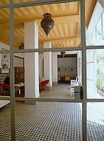 View through a glass door from the courtyard into the large tiled living area