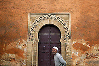 """A man walks in front of doors in walls of Rabat's Medina September 23, 2014. Behind walls of Medina and Kasbah of the Oudayas, ancient neighbourhoods of Morocco's capital, labyrinths of small alleys, colourful buildings and street markets offer a glimpse into city's rich history. Rabat was recently listed by UNESCO as a World Heritage Site and suggested as a """"must see"""" destination by major media outlets and tourist agencies.  REUTERS/Damir Sagolj (MOROCCO)"""