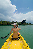 Paddling sit-on-top kayak in the brilliant green waters of Bocas Del Toro, Panama