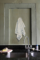 A whimsical trompe l'oeil of a tea towel by Ian Harer on one of the green panels above the kitchen sink