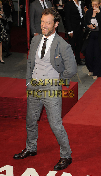 Jude Law.The World Premiere of 'Anna Karenina', The Odeon Leicester Square, London, England..4th September 2012.full length grey gray suit beard facial hair waistcoat smiling hand arm mouth open funny laughing .CAP/CAN.©Can Nguyen/Capital Pictures.
