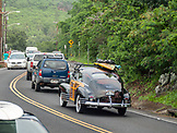USA, Hawaii, Oahu, an old woody with a surfboard on the roof drives on the road around Waimea Bay, the North Shore of Oahu