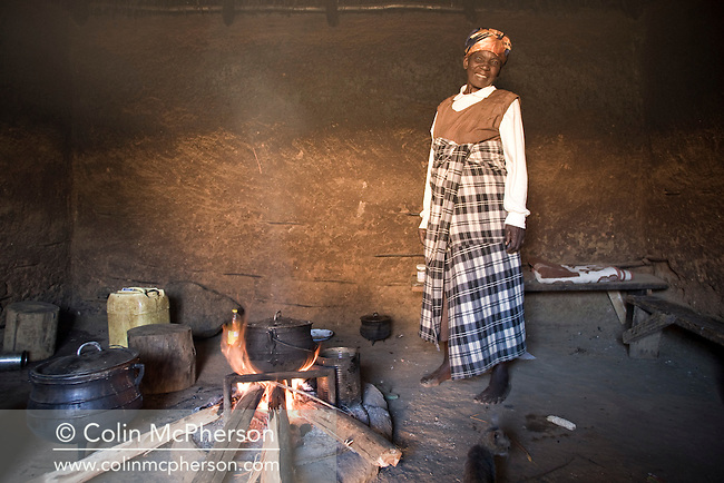 An old woman smiling and standing beside her kitchen fire in a hut at her farm stockade in Pine Valley, Swaziland. The Kingdom of Swaziland (population 1.1m), a small, landlocked country in southern Africa was bordered by South Africa on three sides and Mozambique to the east, with Mbabane as its administrative capital. At the start of the 21st century, the country had the highest incidence per head of population of HIV/Aids in the world and and high levels of poverty mainly in rural areas where 75 per cent of the population lived.