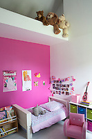 A girl's bedroom in shocking-pink and white contains child-size scaled down furniture such as the bed and armchair