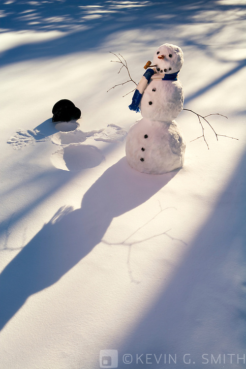 Snowman with blue and white stripped sccarf standing next to snow angel it made, top hat left in the snow, tree shadows in the snow in background.