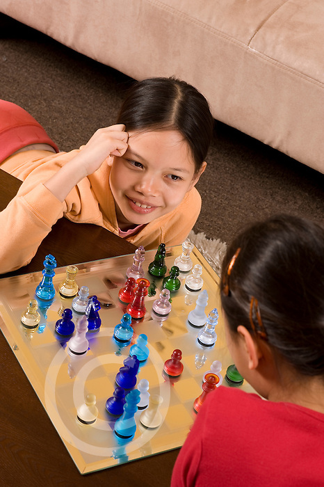 9 year old girl playing chess with 8 year old friend Filipina and  Vietnamese American vertical