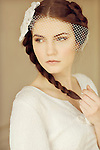 Portrait of young woman with bridal headpiece and braided hair looking over her shoulder