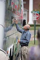 "NWA Democrat-Gazette/J.T. WAMPLER Paul LeBlanc of Fayetteville signs the bus Sunday Sept. 13, 2015 during the fourth national ""Nuns on the Bus"" tour at St. Paul's Episcopal Church in Fayetteville. <br /> <br /> ((SEE 001 PHOTO FOR EXTENDED CUTLINE INFO))"