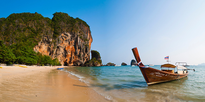 Panoramic Photo of a Traditional Thai Boat on Tropical Ao Phra Nang Beach, Railay (Rai Leh), South Thailand. This panoramic photo shows a traditional Thai boat at Ao Phra Nang Beach in the Railay Beach area of south Thailand. Railay Beach (Rai Leh Beach) area is a stunning Thai holiday destination near Krabi, on the Andaman Coast of Thailand. The tropical paradise of Railay (Rai Leh), only accessible by traditional Thai boat due to being surrounded by enormous rocky limestone karsts, is home to a number of beautiful exotic beaches including Ao Phra Nang, East Railay, and West Railay Beach.