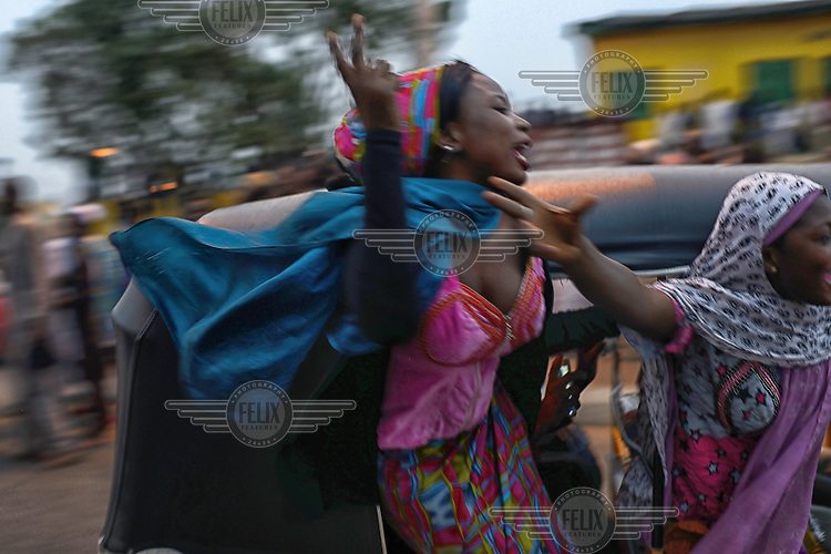 Women hang from the side of a tuk-tuk (known in the country as a 'keke-marwas') as they join in celebrations of the victory of Muhammadu Buhari, leader of the APC (All Progressives Congress Party), in the 2015 Nigerian Presidential elections.