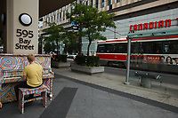 Toronto (ON) CANADA - July 2012 - A stranger play the piano  in downtown Toronto . <br /><br />These pianos scattered around the city are loans from various countries that will take part in the 2015 Pan American games.