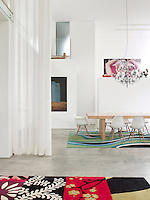 An inspiring, open plan living and dining space with a double height ceiling. The dining area, separated by a sheer curtain, has a simple pine wood table and white Eames dining chairs. They stand on a vibrant carpet entitled Alice in Wonderland from Carpet Diem.