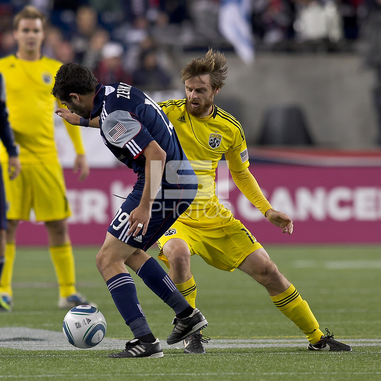 New England Revolution midfielder Monsef Zerka (19) dribbles as Columbus Crew midfielder Eddie Gaven (12) defends. In a Major League Soccer (MLS) match, the Columbus Crew defeated the New England Revolution, 3-0, at Gillette Stadium on October 15, 2011.