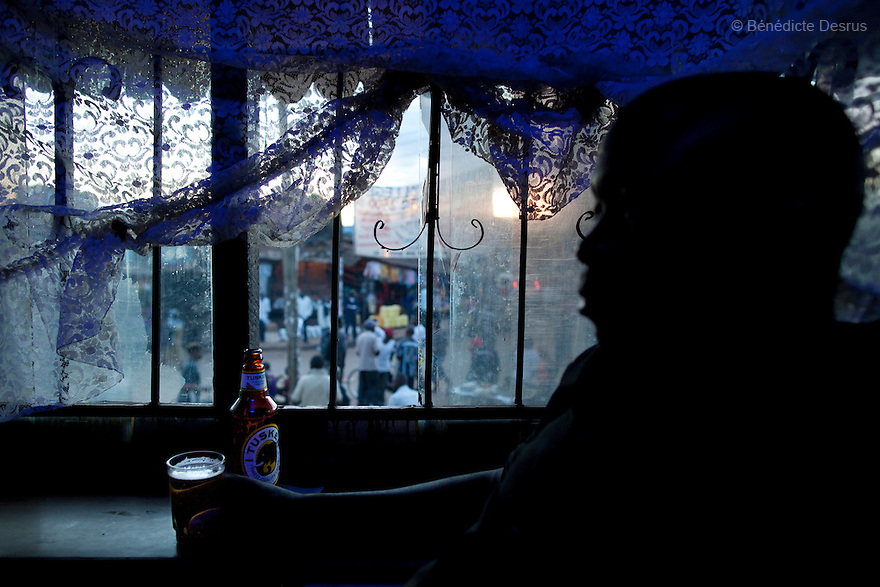 Kenyans drink beer in a bar during happy hour in a Nairobi slum on March 22, 2013 (Photo by Benedicte Desrus)