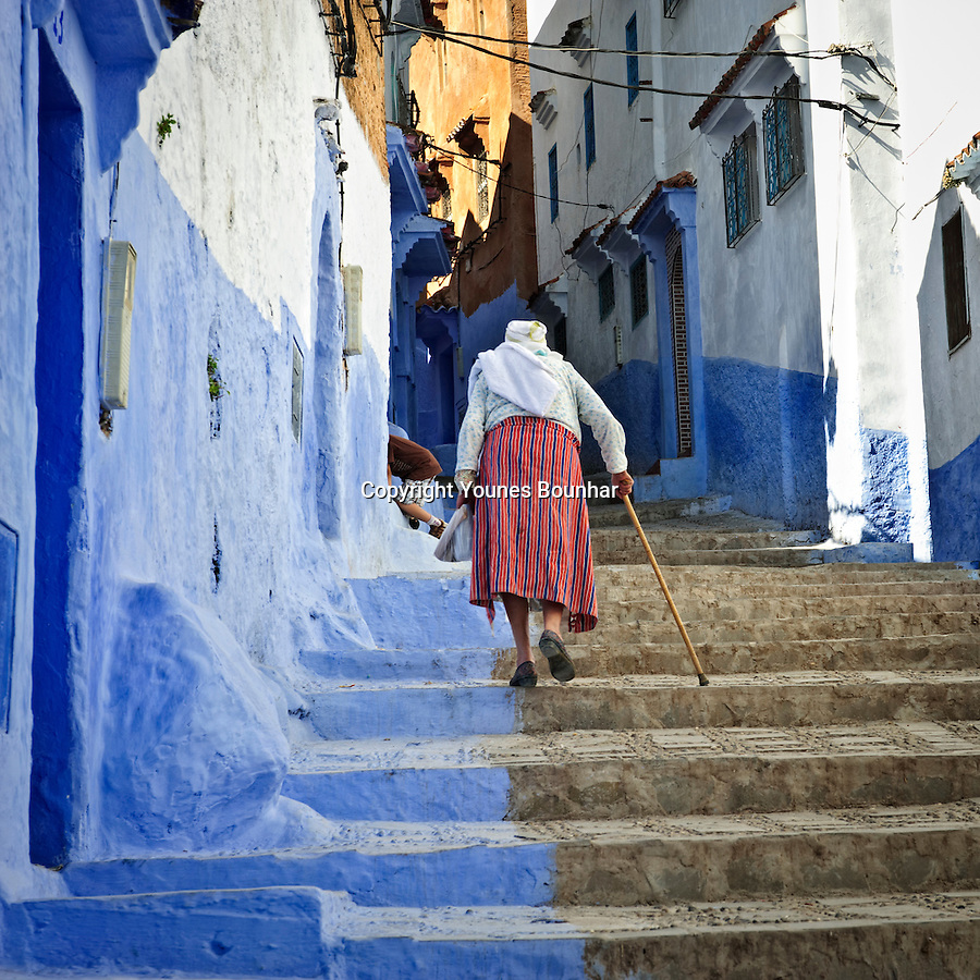 An elderly woman in traditional northern dress slowly makes her way up a steep stairway in the mesmerizing blue streets of Chefchaouen (at the foot of the Rif mountains of Morocco)