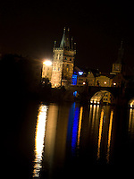 The Charles Bridge crossing the Vltave river leads to the Malá Strana District through the Old Town Bridge Tower in Prague, Czech Republic.