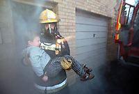 Firefighters in breathing apparatus. On their tunics are  right angled intrinsically safe torchs. There are also  A.D.S.U., an automatic distress signialling unit, which is part of their B.A. sets. This unit emits a very loud whistle should the firefighters remain motionless for a short period. Therefore, if they are trapped the unit will sound and will allow other firefighters to locate them. They have just rescued a young child from a first floor bedroom house fire. The fire had taken control of building and the firefighters were searching in temperatures in excess of 1000 degrees centigrade. ..© SHOUT. THIS PICTURE MUST ONLY BE USED TO ILLUSTRATE THE EMERGENCY SERVICES IN A POSITIVE MANNER. CONTACT JOHN CALLAN. Exact date unknown.john@shoutpictures.com.www.shoutpictures.com.