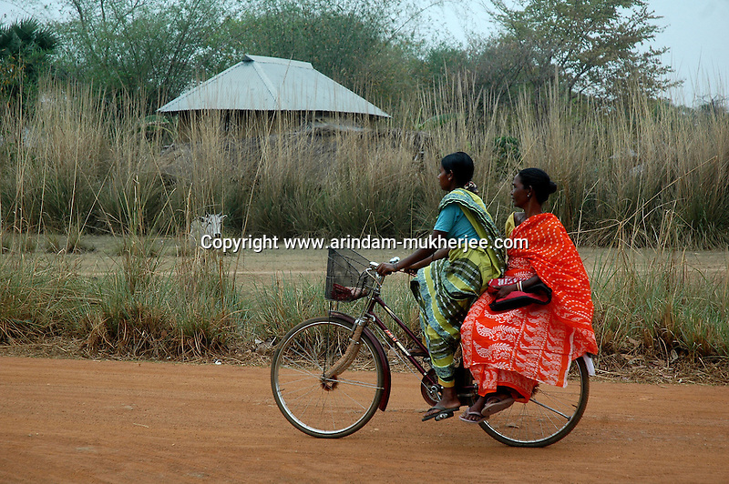 Indian rural women going for work on a bycycle in a village 200 Kms away from. Kolkata, West Bengal, India.  ARINDAM MUKHERJEE