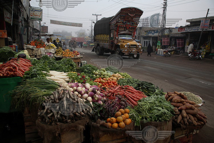 A large freight truck rolls past a fruit and vegetable market in Multan.